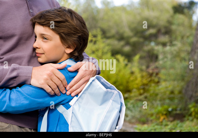 boy cuddling dad back from school - Stock Image