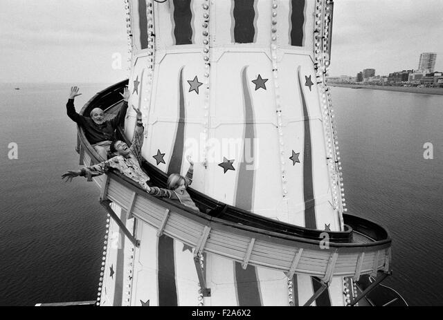 Brighton Artist Philip Dunn, Punch and Judy man Sgt Stone and a Brighton schoolgirl on the helter skelter ride on - Stock Image