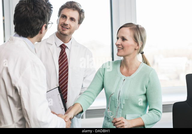 Woman shaking hands with man wearing lab coat - Stock Image