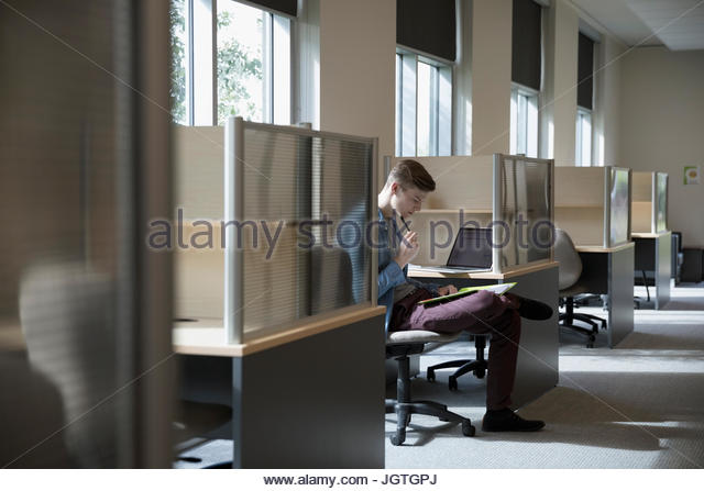 Male college student studying at desk in library - Stock Image