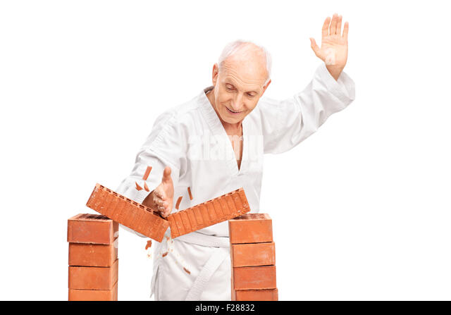 Studio shot of a senior man in a white kimono breaking a brick with his bare hand isolated on white background - Stock Image
