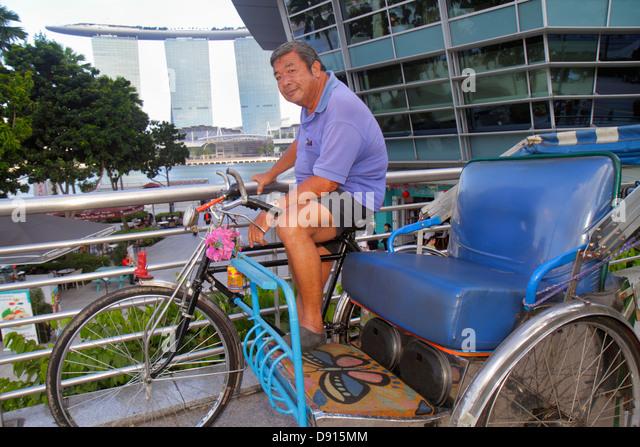 Singapore Singapore River Marina Bay One Fullerton Asian man Marina Bay Sands Integrated Resort Skybridge bicycle - Stock Image