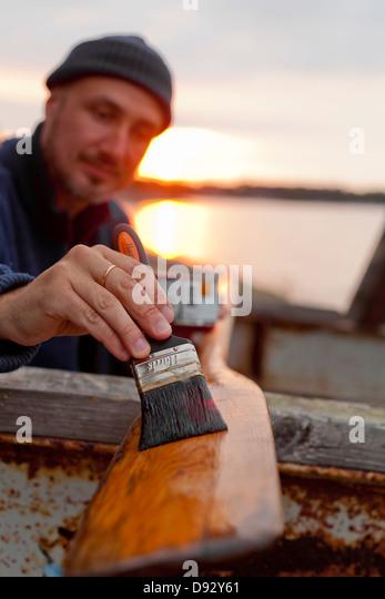 Man painting oar - Stock Image