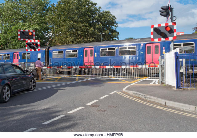 Railway train crossing road with level crossing and bicycle and car waiting - Stock Image