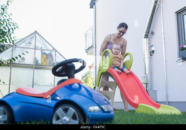 Mother assisting her son on slide, Munich, Bavaria, Germany - Stock Image