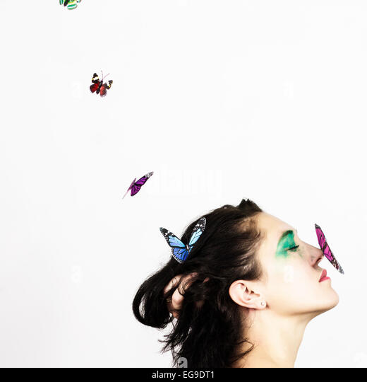 Woman with butterfly on her nose - Stock Image
