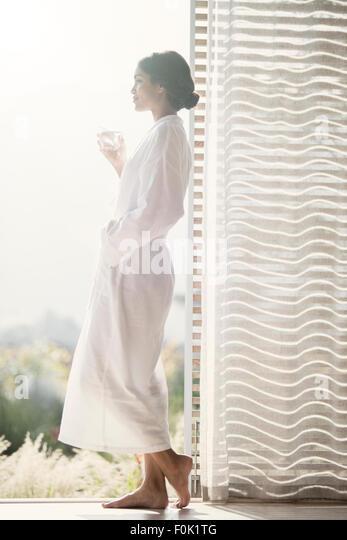 Woman in bathrobe drinking water at open door - Stock Image