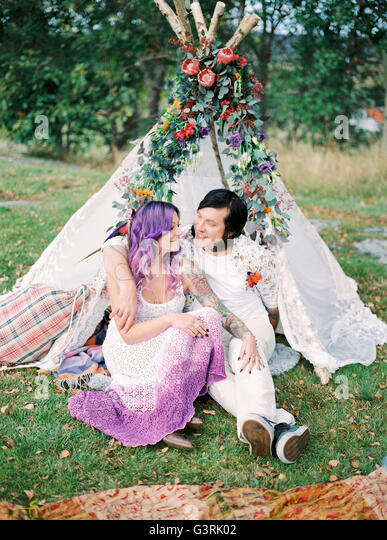 Sweden, Bride and groom sitting on grass in front of white tent at hippie wedding - Stock Image