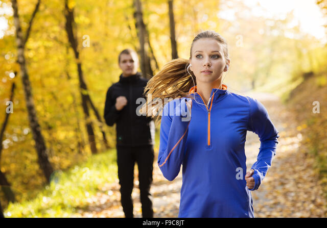 Young running couple jogging in autumn nature - Stock Image