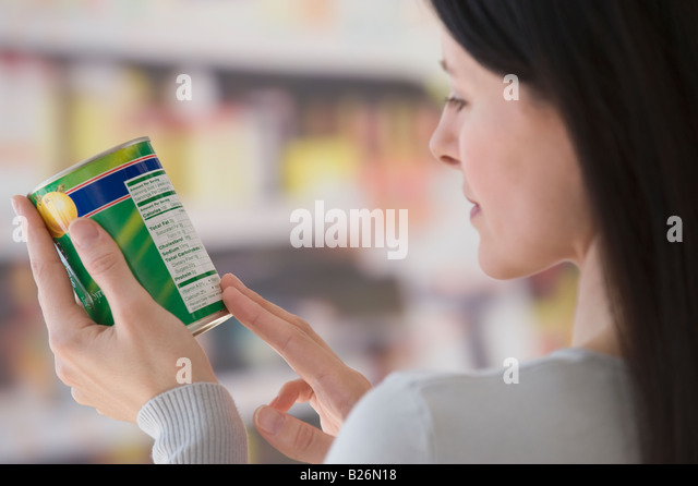 Woman reading label at grocery store - Stock Image
