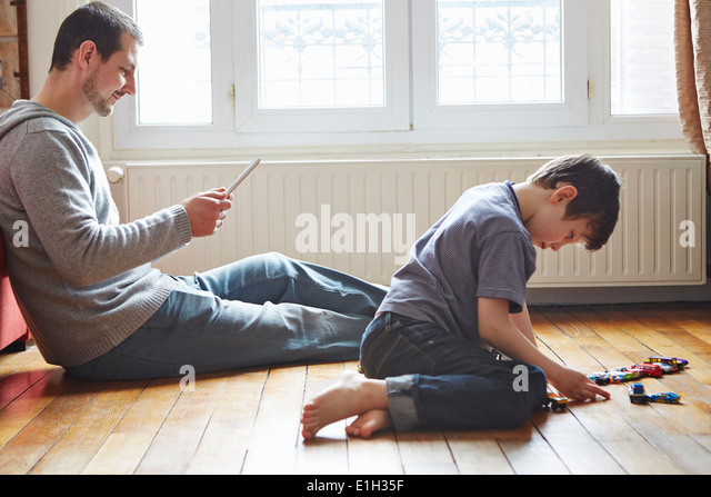 Father and son spending time in living room - Stock Image