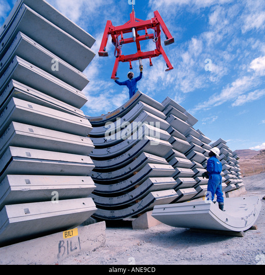 Workers stacking pre-cast steel reinforced concrete  segments used to line a tunnel on the Lesotho Highlands Water - Stock Image