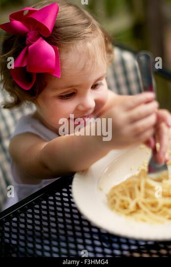 High angle vew of girl with pink hair bow sitting at garden eating spaghetti - Stock Image