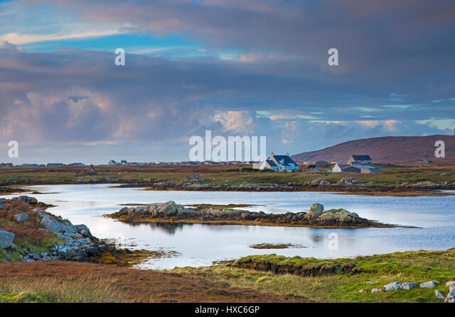 Tranquil scene clouds over lake and fishing village, Lochboisdale, South Uist, Outer Hebrides - Stock Image