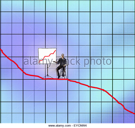 Businessman giving a presentation of growth chart while sitting on decreasing line graph - Stock Image