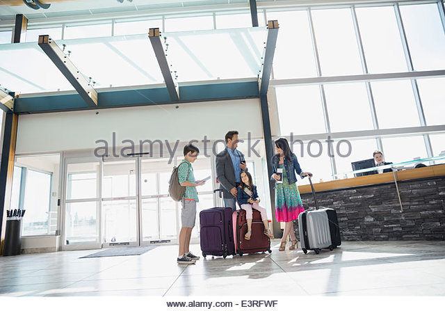 Family with suitcases arriving at airport - Stock Image