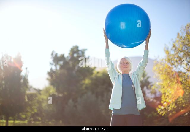 Senior woman holding fitness ball in park - Stock Image