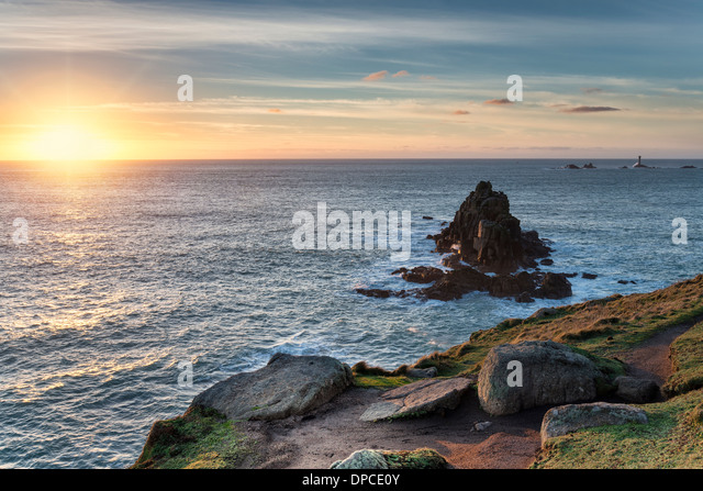 Rocky cliffs at Lands End in Cornwall with the Longships lighthouse in the distance - Stock-Bilder