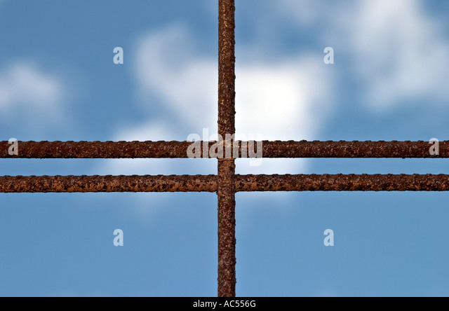 Corroded concrete reinforcing mesh against blue sky - Stock Image