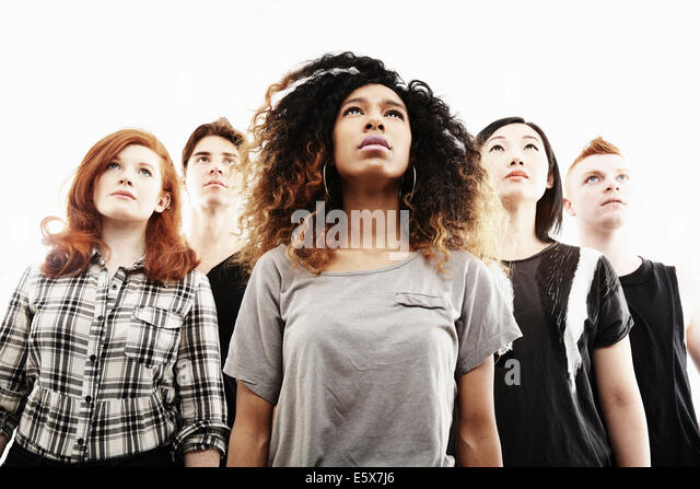Low angle studio portrait of five young adults looking upward - Stock Image