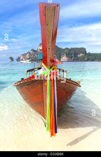 Old traditional wooden boat on a tropical island in Thailand. - Stock Image
