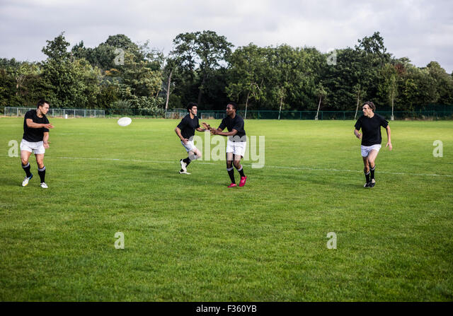 Rugby players training on pitch - Stock Image