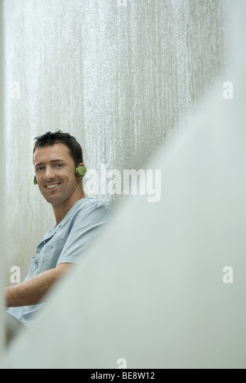 Man listening to headphones, smiling at camera - Stock Image