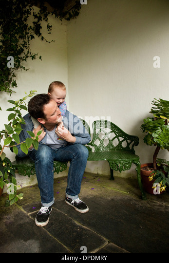 Child riding piggyback on father in garden - Stock Image