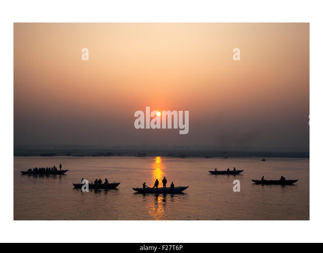 Tourists float down the Ganges River at sunrise in Varanasi, India - Stock Image