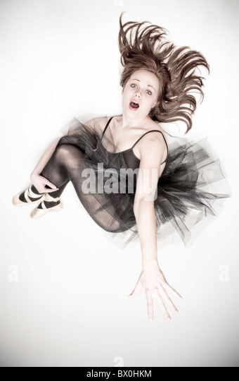 A teenage caucasian ballerina wearing a black tutu jumps in the air. - Stock Image