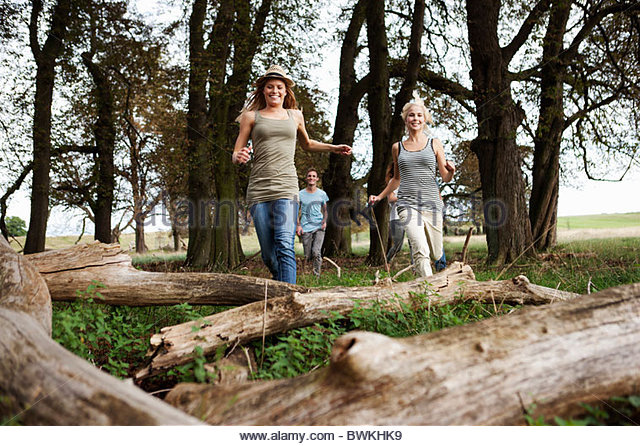 Young persons running in woods - Stock Image