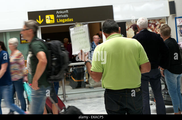Holiday rep hotel driver waiting at busy airline passenger arrivals hall at Lanzarote airport Canary Islands Spain - Stock-Bilder