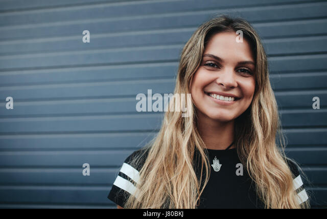 Close up portrait of smiling young female standing against gray wall. Beautiful caucasian young woman looking at - Stock Image