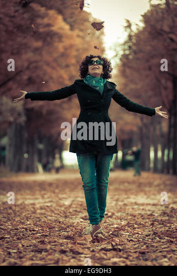 Woman throwing leaves in the air - Stock Image