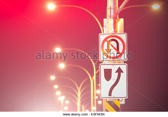 Road Signs And Illuminated Street Lights - Stock Image