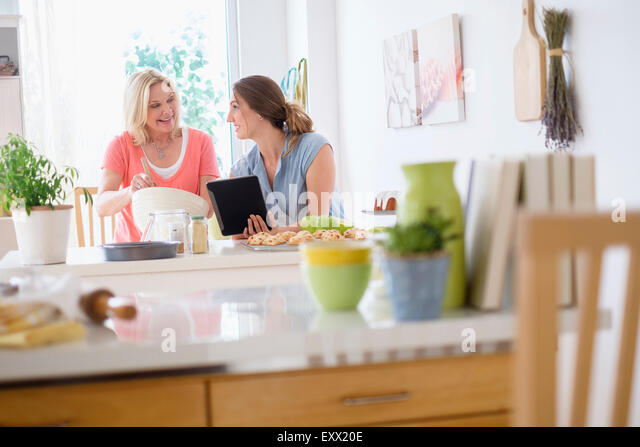 Mother with adult daughter baking in kitchen - Stock Image