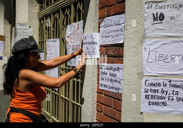 A woman places a poster against the Constituent Assembly in Caracas, Venezuela, 24 July 2017. Venezuela's Constituent - Stock Image