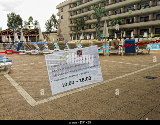 Tenerife holiday pool open only between 10am and 6pm. To prevent towels being put onto sunbeds prior - Stock Image
