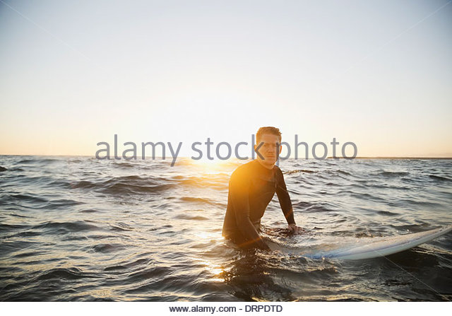 Portrait of man sitting on surfboard - Stock Image