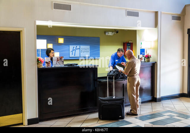 North Carolina NC Morehead City Holiday Inn Express hotel front desk reservations clerk guest luggage - Stock Image