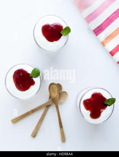 healthy yogurt parfait with jam in glass on white table - Stock Image