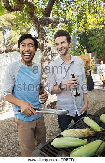 Smiling men drinking beer and barbecuing corn cobs - Stock-Bilder