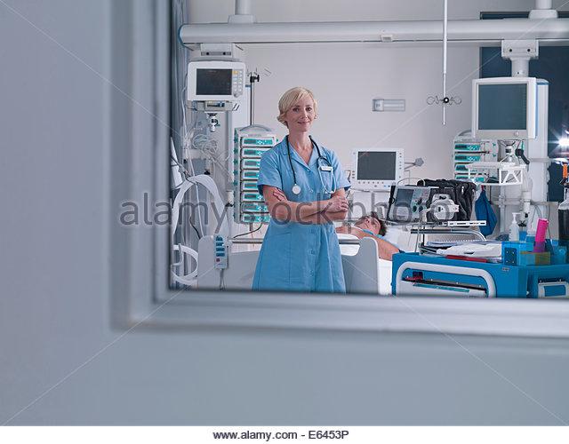Nurse tending patient in intensive care - Stock Image