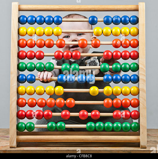 Baby Girl behind Abacus - Stock Image