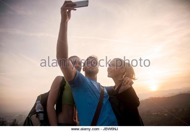 Three friends outdoors, wearing sports clothing, taking selfie, using smartphone - Stock-Bilder