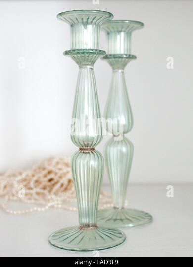 green glass candle stick holders and pearl necklace on shelf - Stock Image