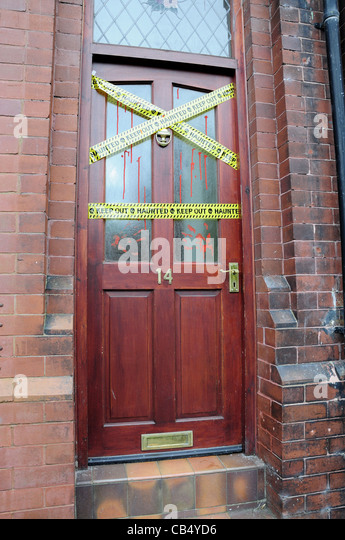 Front door with haunted stickers across it and fake bloody handprints - Stock Image