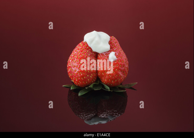 Single fresh Strawberry topped with natural thick Yogurt - Stock Image