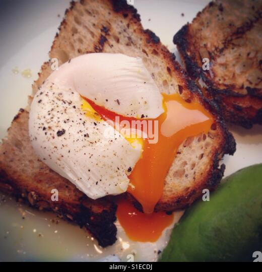 Poached Egg on Toast with Avocado - Stock Image