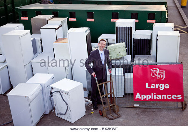 A businessman standing with a trolley in a recycling center - Stock Image